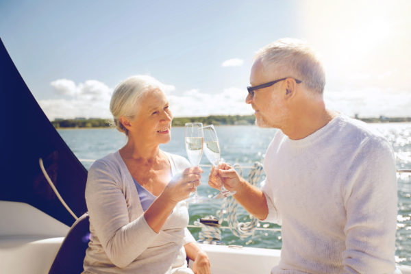 Senior couple clinking champagne on a yacht deck