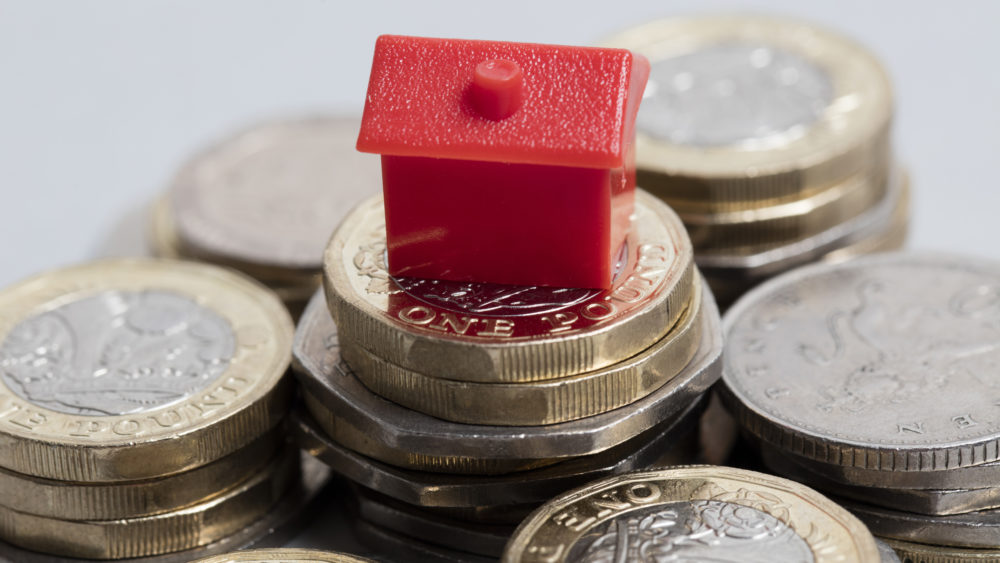 Plastic red house sitting on top of a pile of money